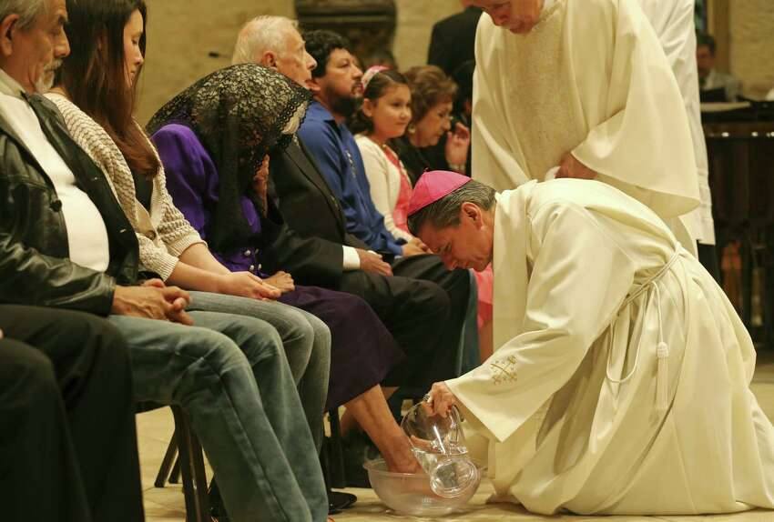 Archbishop Gustavo Garcia-Siller washes Tomasa Luna's feet during Holy Thursday mass held at San Fernando Cathedral Thursday April 17, 2014. Luna was one of 12 people who had their feet washed by Garcia-Siller. The ritual reenacts Jesus washing the feet of his 12 disciples at the Last Supper.