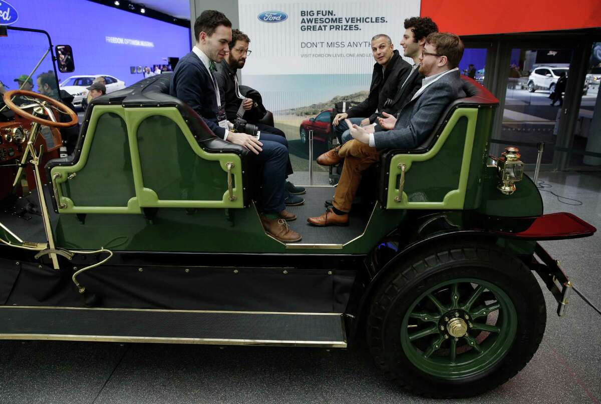 Visitors to the New York International Auto Show sit in an electric carriage prototype in New York, Thursday, April 17, 2014. A prototype of the old-timey electric cars that Mayor Bill de Blasio would like to take the place of horse-drawn carriages on New York City streets will be unveiled at the New York Auto Show on Thursday. (AP Photo/Seth Wenig) ORG XMIT: NYSW126