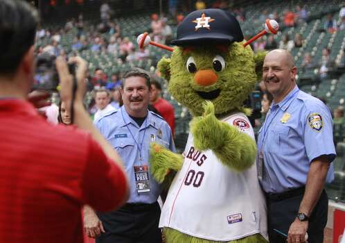 Houston Fire Dept. spokesman Capt. Ruy Lozano, left, takes a photo of Engineer Operator Dwayne Wyble and Senior Captain Brad Hawthorne, right, as they pose with Astros mascot Obit. Photo: Melissa Phillip, Houston Chronicle