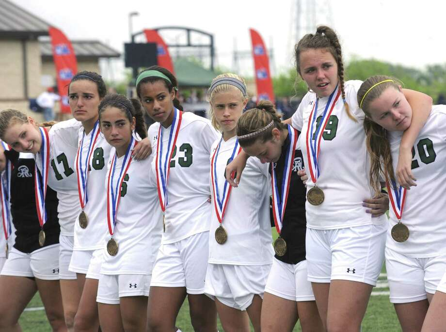 Reagan girls soccer players wear their 5A state semifinalist medals after losing 3-0 to two-time defending champion Plano West. Photo: Billy Calzada / San Antonio Express-News / San Antonio Express-News