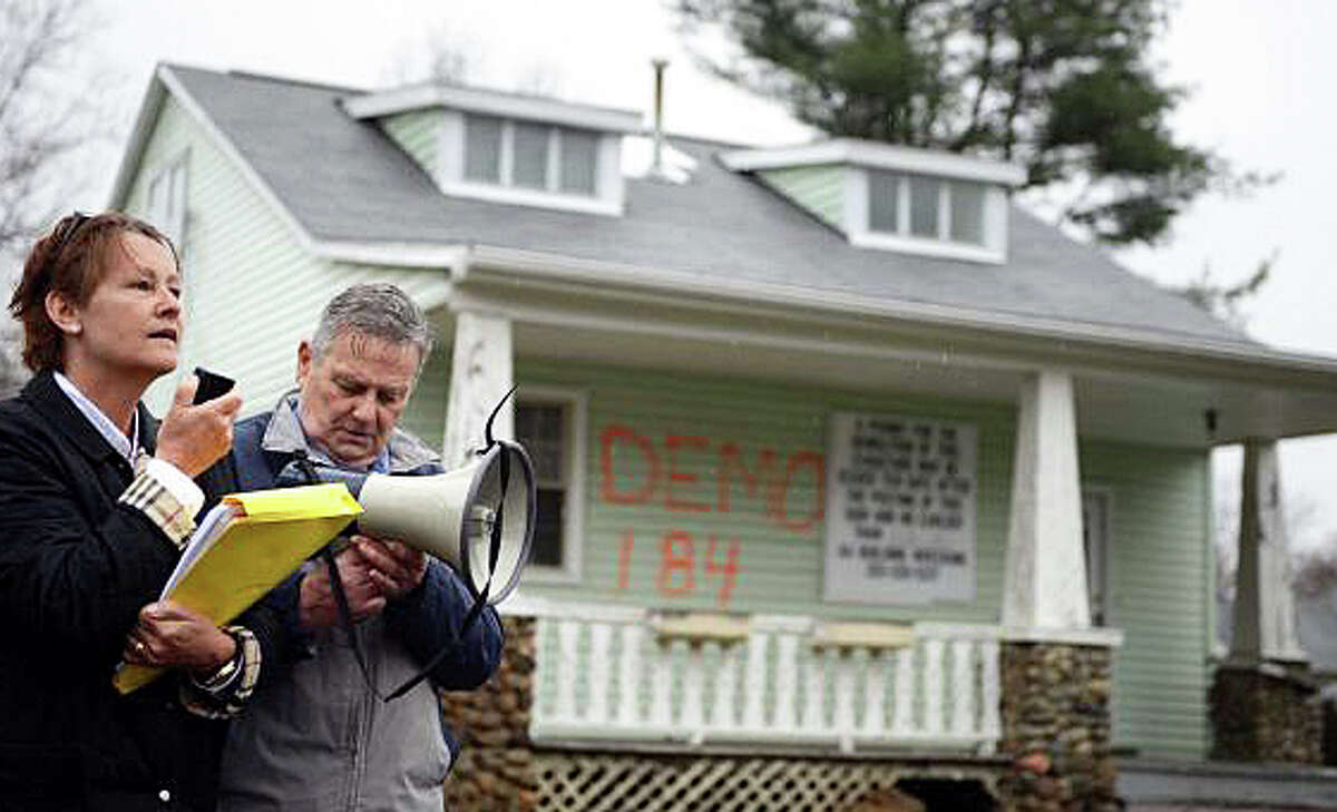 Fairfielder Melanie Marks and Edwards Collins of Milford protest the planned demolition of the former home of aviation pioneer Gustave Whitehead outside the Alvin Street house on Tuesday.