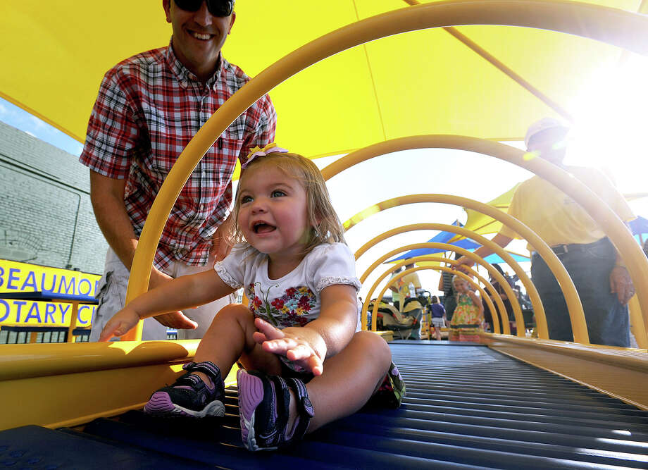 Kassidy Lewis, 1, glides across a horizontal slide at the new playground next to the downtown Event Centre in Beaumont on Tuesday. Now open to the public, the facility offers equipment for special needs kids. Photo taken Tuesday, September 24, 2013 Guiseppe Barranco/The Enterprise Photo: Guiseppe Barranco, STAFF PHOTOGRAPHER / The Beaumont Enterprise