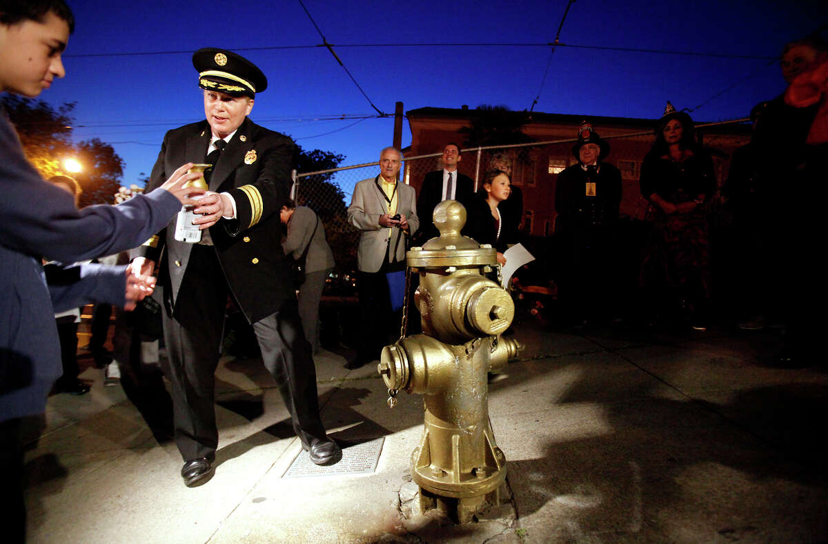 Fire Chief Joanne Hayes-White hands off the spray paint to coat the gold hydrant at last year's ceremony.
