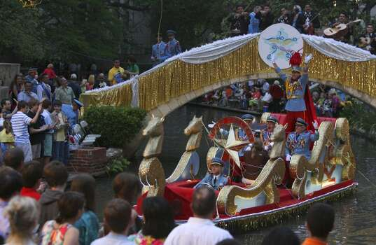 King Antonio's float enters the Arneson River Theater area Monday night during the Texas Cavaliers' River Parade. Standing on the back of the float waving his arms is the 88th King Antonio, Nick Campbell. JOHN DAVENPORT/jdavenport@express-news.net Photo: John Davenport, Express-News