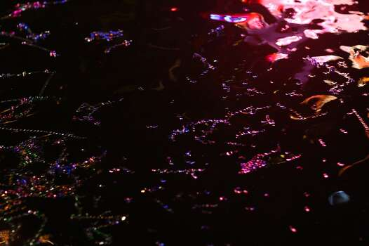 Colored lights from a passing float reflect on confetti floating in the river during theTexas Cavaliers River Parade, Monday, April 19, 2010. Jennifer Whitney/ special to the Express-News Photo: Jennifer Whitney, Special To Express-News