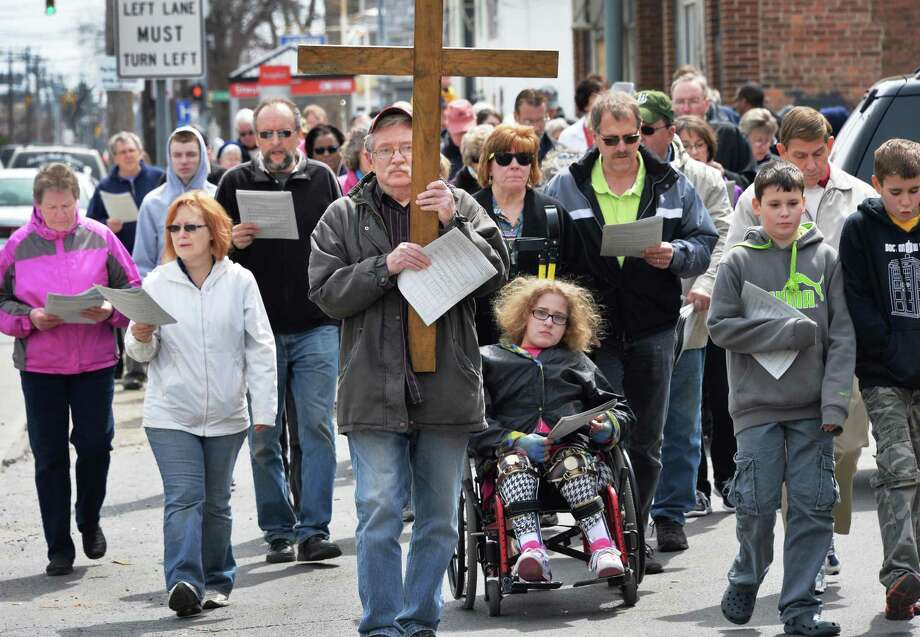 Peter Healey of Schenectady carries a cross as the Christ Church 19th annual Public Stations of the Cross makes its way along State Street Friday,  April 18, 2014, in Schenectady, N.Y. Parishioners made stops throughout Schenectady where they recounted the suffering and death of Jesus Christ. The traditional Good Friday procession started at Christ Church on State St., and made stops outside churches, community centers and the Schenectady County Jail before concluding at Schenectady City Mission. (John Carl D'Annibale / Times Union) Photo: John Carl D'Annibale / 00026527A