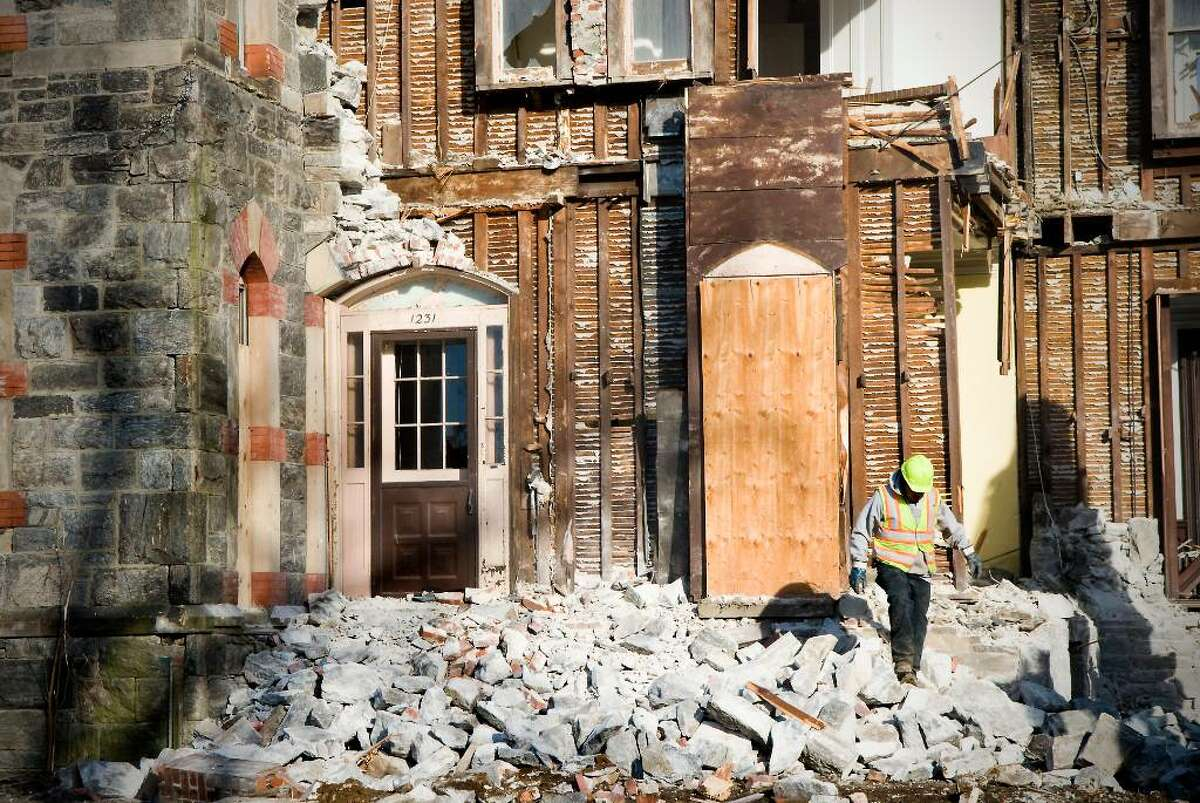 Employees of City Carting & Recycling begin demolition on St. Andrew's rectory in Stamford, Conn. on Thursday, Feb. 11, 2010.