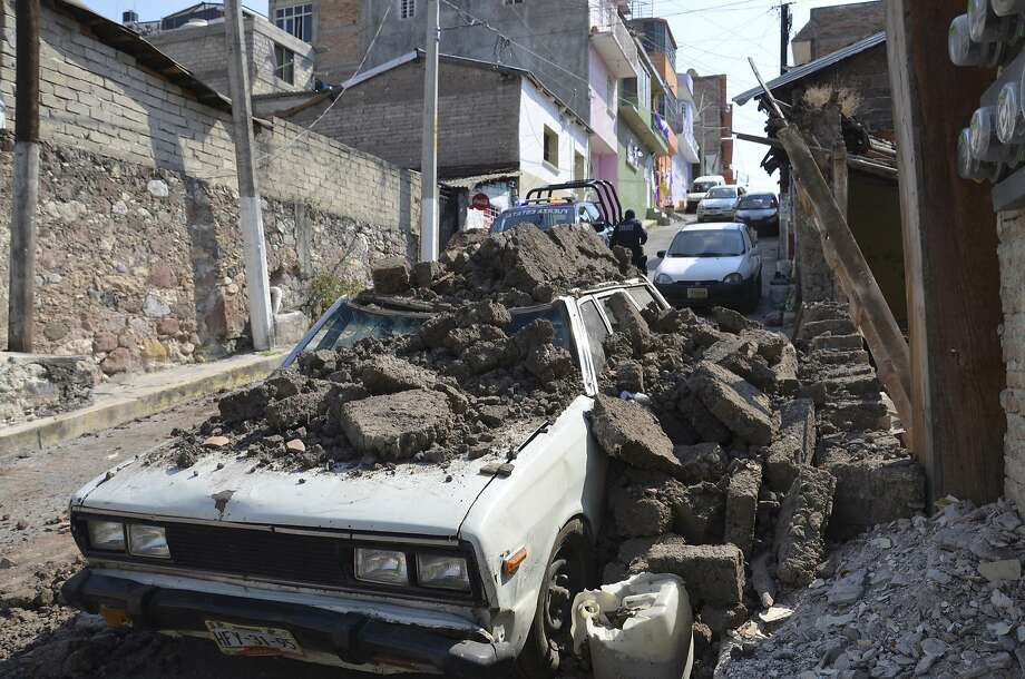 A parked car suffered damage when a adobe wall collapsed on it after a strong earthquake shook Chilpancingo, Mexico, Friday morning, April 18, 2014. A powerful magnitude-7.2 earthquake shook central and southern Mexico but there were no early reports of major damage or casualties. (AP Photo/Alejandrino Gonzalez) Photo: Alejandrino González, Associated Press