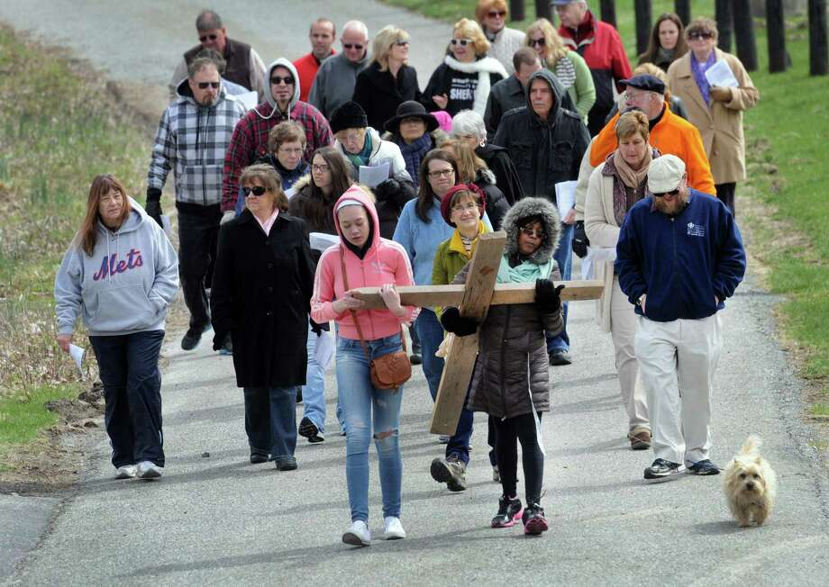 Leanna Murphy, 16, and her mother Donna Murphy, of Brookfield, carry the cross in an annual Good Friday observance. The Passion and death of Jesus Christ is remembered Friday, April 18, 2014, with an ecumenical Good Friday Cross Walk led by area clergy in Brookfield, Conn. Starting and ending at the Brookfield Congregational Church, worshippers took turns carrying the cross, singing hymns and listening to short observances along the way. Easter, when the resurrection of Christ is celebrated, is Sunday. Photo: Carol Kaliff / The News-Times