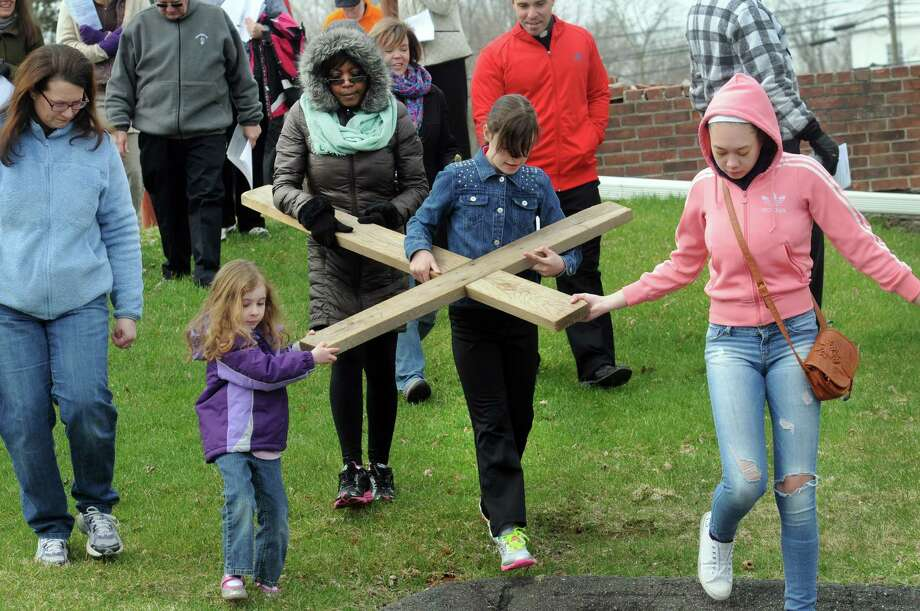 From left, Hannah Keating, 4 1/2, Donna Murphy, Abigail Warner and Leanna Murphy, 16, take a turn at carrying the cross. The Passion and death of Jesus Christ is remembered Friday, April 18, 2014, with an ecumenical Good Friday Cross Walk led by area clergy in Brookfield, Conn. Starting and ending at the Brookfield Congregational Church, worshippers took turns carrying the cross, singing hymns and listening to short observances along the way. Easter, when the resurrection of Christ is celebrated, is Sunday. Photo: Carol Kaliff / The News-Times