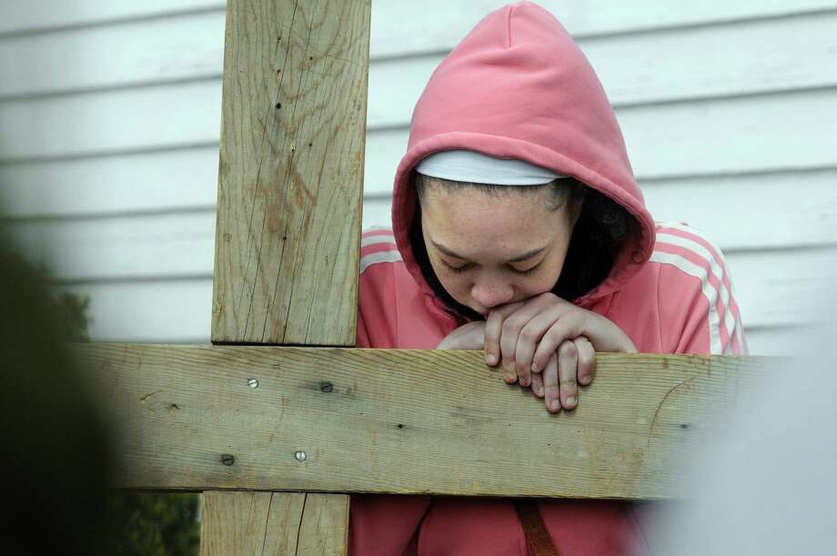Leanna Murphy, 16, of Brookfield, leans on the cross Friday morning during a Good Friday's Cross Walk.The Passion and death of Jesus Christ is remembered Friday, April 18, 2014, with an ecumenical Good Friday Cross Walk led by area clergy in Brookfield, Conn. Starting and ending at the Brookfield Congregational Church, worshippers took turns carrying the cross, singing hymns and listening to short observances along the way. Easter, when the resurrection of Christ is celebrated, is Sunday. Photo: Carol Kaliff / The News-Times