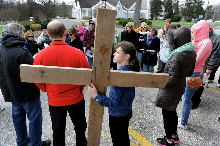 Abigail Warner, 10 1/2, of Brookfield, Holds the cross during a Good Friday Cross Walk in Brookfield. The Passion and death of Jesus Christ is remembered Friday, April 18, 2014, with an ecumenical Good Friday Cross Walk led by area clergy in Brookfield, Conn. Starting and ending at the Brookfield Congregational Church, worshippers took turns carrying the cross, singing hymns and listening to short observances along the way. Easter, when the resurrection of Christ is celebrated, is Sunday. Photo: Carol Kaliff / The News-Times