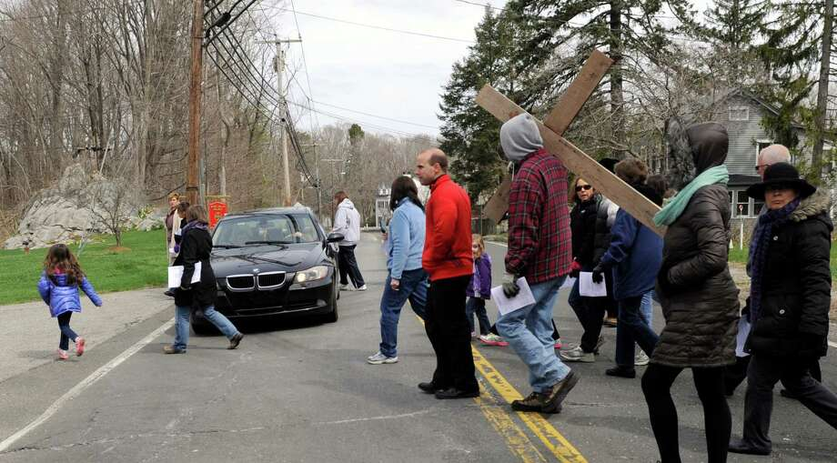 Cars stop to allow a Good Friday Cross Walk to cross the street on Route 25 in Brookfield, Friday morning. The Passion and death of Jesus Christ is remembered Friday, April 18, 2014, with an ecumenical Good Friday Cross Walk led by area clergy in Brookfield, Conn. Starting and ending at the Brookfield Congregational Church, worshippers took turns carrying the cross, singing hymns and listening to short observances along the way. Easter, when the resurrection of Christ is celebrated, is Sunday. Photo: Carol Kaliff / The News-Times