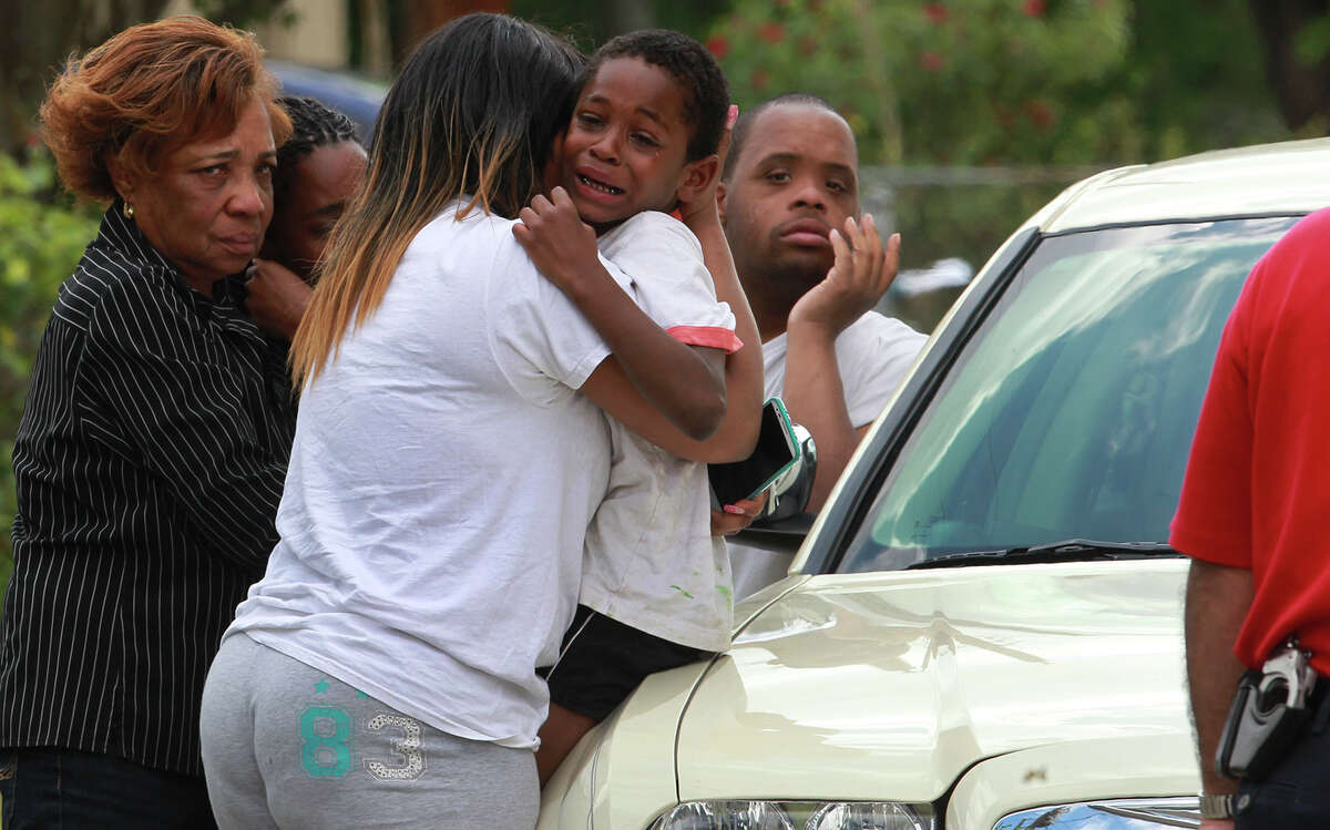 Seven-year-old Kashion Johnson (center) is consoled Friday April 18, 2014 after the boy went missing from a home on the 800 block of Sterling about 1:30 am. . A family friend (not pictured) who lived blocks away later arrived with the child. A witness said the boy was locked out of the house and threw rocks at the house to get his mother to let him back in. The boy's mother was detained by police after she became belligerent.