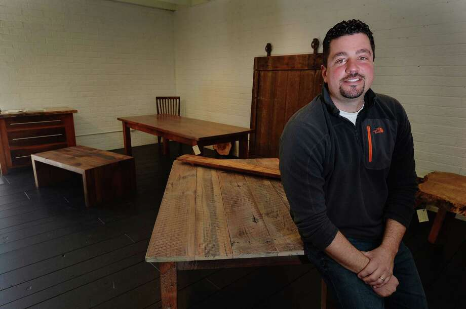Eco-friendly reclaimed wood is popular for all kinds of projects in the home because of its beauty. It's also a durable material. Here, Jonathan Kauffman, of Kauffman & Co, Crafters of Fine Furniture sits in the showroom in Charlotte, N.C., Feb. 3, 2014. (T. Ortega Gaines/Charlotte Observer/MCT) ORG XMIT: 1151420 Photo: T. Ortega Gaines / Charlotte Observer