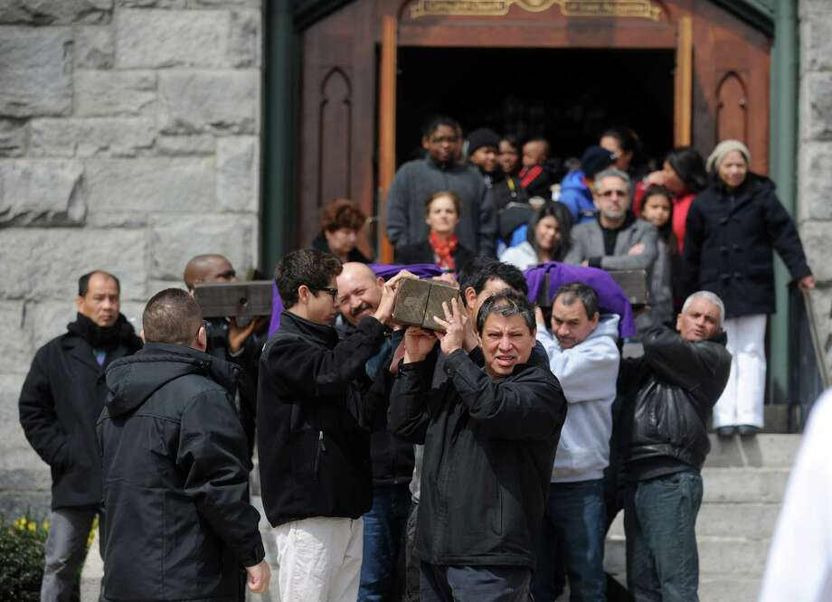 Parishioners carry the cross out of St. Augustine Cathedral during the Good Friday Passion of the Lord Multi-lingual Stations of the Cross Procession to St. Patrick Church Friday, April 18, 2014, in Bridgeport, Conn. Photo: Autumn Driscoll / Connecticut Post