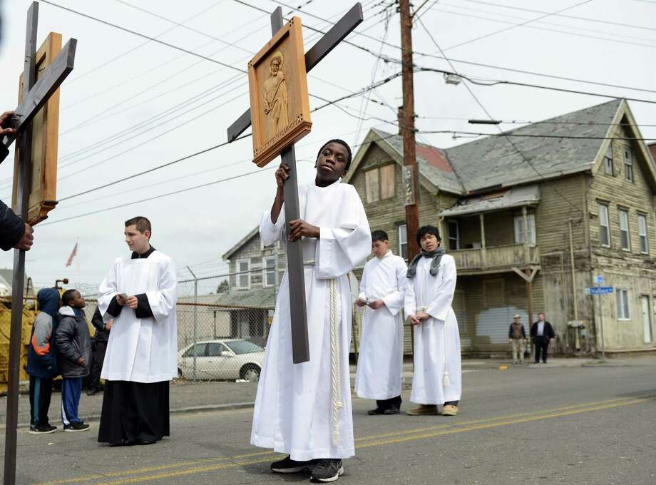 Thirteen-year-old Alexander Lake, of Bridgeport, carries a cross during the Good Friday Passion of the Lord Multi-lingual Stations of the Cross Procession from St. Augustine Cathedral to St. Patrick Church Friday, April 18, 2014, in Bridgeport, Conn. Photo: Autumn Driscoll / Connecticut Post