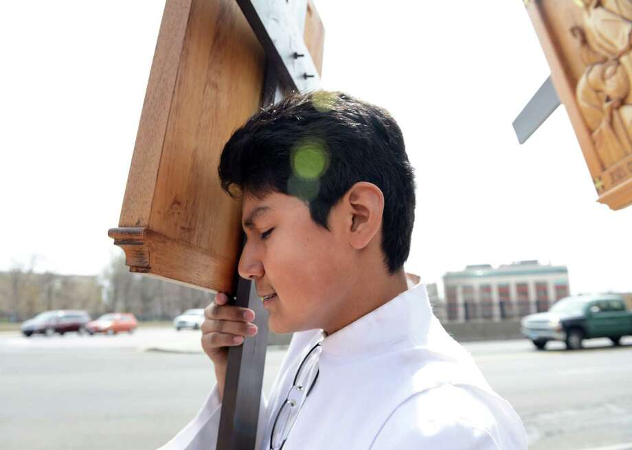 Thirteen-year-old Elton Tonacatl, of Bridgeport, carries a cross during the Good Friday Passion of the Lord Multi-lingual Stations of the Cross Procession from St. Augustine Cathedral to St. Patrick Church Friday, April 18, 2014, in Bridgeport, Conn. Photo: Autumn Driscoll / Connecticut Post