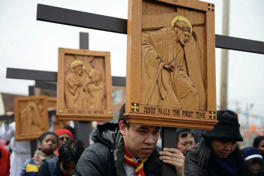 Minhtam Nguyen, of Bridgeport, kneels during the Good Friday Passion of the Lord Multi-lingual Stations of the Cross Procession from St. Augustine Cathedral to St. Patrick Church Friday, April 18, 2014, in Bridgeport, Conn. Photo: Autumn Driscoll / Connecticut Post
