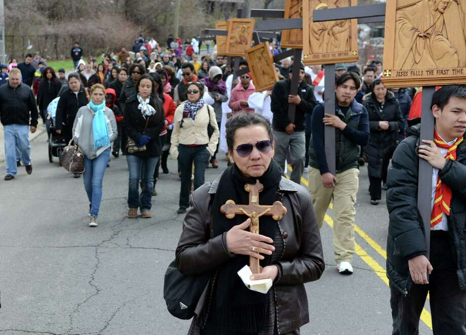 Decey Morales, of Bridgeport, carries a wooden crucifix during the Good Friday Passion of the Lord Multi-lingual Stations of the Cross Procession from St. Augustine Cathedral to St. Patrick Church Friday, April 18, 2014, in Bridgeport, Conn. Photo: Autumn Driscoll / Connecticut Post