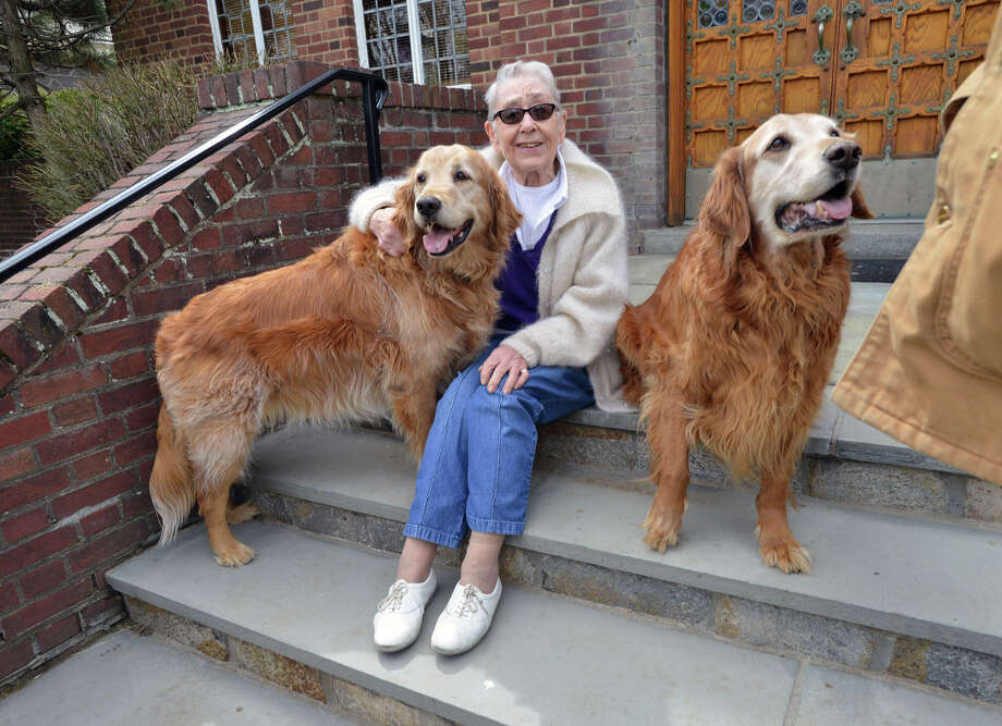 Margaret Casey, 86, of Greenwich, with golden retrievers, Clancy, left, and Chase at St. Mary Church in Greenwich, Conn., Friday, April 18, 2014.