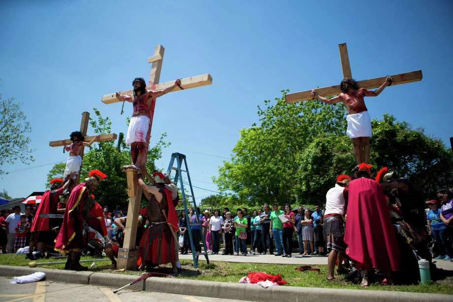 Jesus Estrada, center, performs the passion of Christ during the Queen Of Peace Catholic Church re-enactment of La Via Crucis, surrounded by the thieves Christ died next to. Friday, April 18, 2014, in Houston. Hundreds of faithfuls gathered to reaffirm their faith. Photo: Marie D. De Jesus, Houston Chronicle / © 2014 Houston Chronicle
