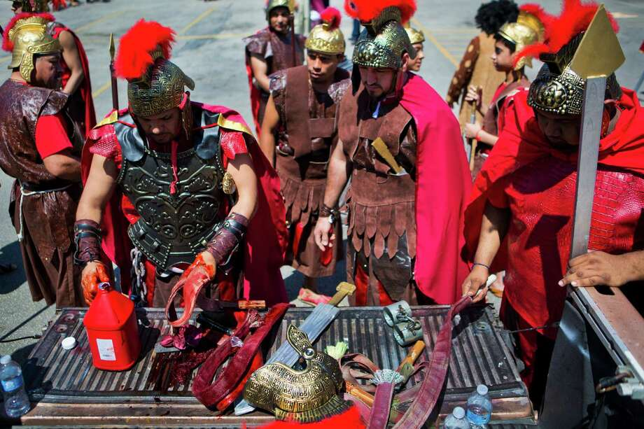 Members of the Queen Of Peace Catholic Church dressed as Roman soldiers paint their torture props with theatric blood in preparation for the re-enactment of the La Via Crucis, Friday, April 18, 2014, in Houston. Photo: Marie D. De Jesus, Houston Chronicle / © 2014 Houston Chronicle