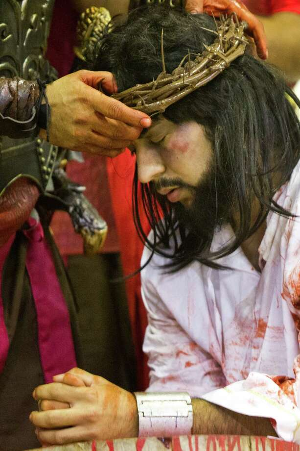 Jesus Estrada performs the moment Christ is crowned with thorns by Roman soldiers during the re-enactment of La Via Crucis by members of the Queen Of Peace Catholic Church, Friday, April 18, 2014, in Houston. Photo: Marie D. De Jesus, Houston Chronicle / © 2014 Houston Chronicle