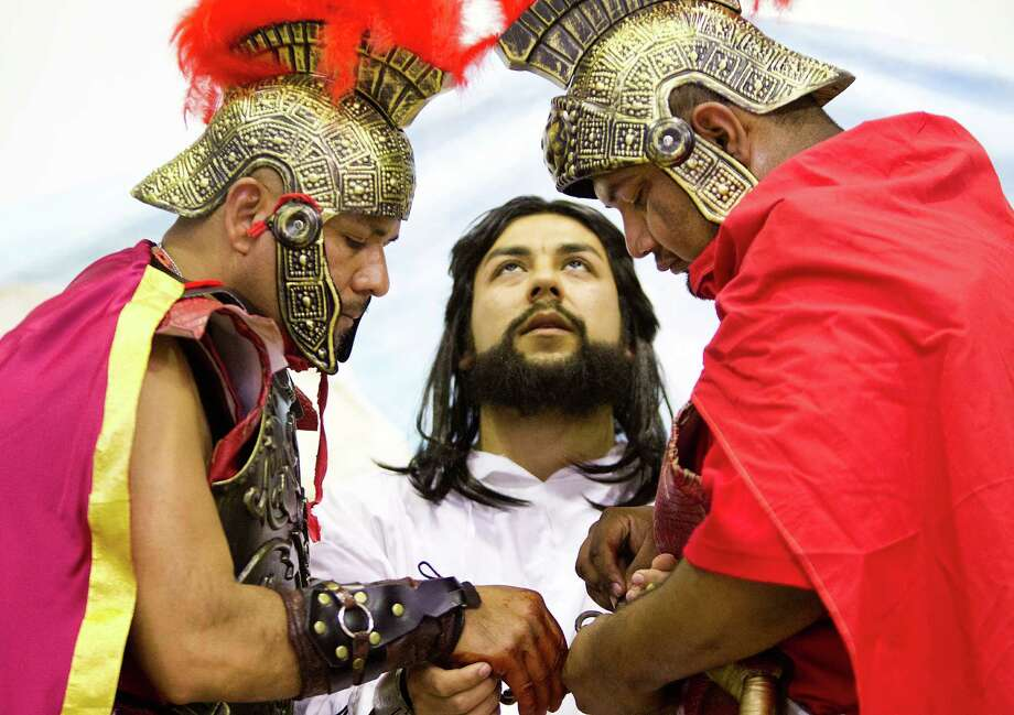 Jesus Estrada, center, performs the moment Christ is apprehended by Roman soldiers during the re-enactment of La Via Crucis by members of the Queen Of Peace Catholic Church, Friday, April 18, 2014, in Houston. Photo: Marie D. De Jesus, Houston Chronicle / © 2014 Houston Chronicle