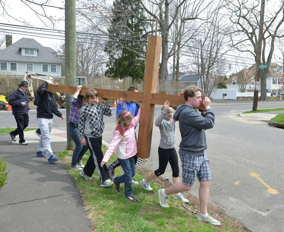 At right, Hans van Rhyn, 13, of Riverside, leads the First Congregational Church of Greenwich Youth Cross Walk in Old Greenwich, Conn., Good Friday afternoon, April 18, 2014. The cross was carried from the church in Old Greenwich to Greenwich Point, where it will be used for the sunrise service on Easter Sunday morning. Photo: Bob Luckey / Greenwich Time