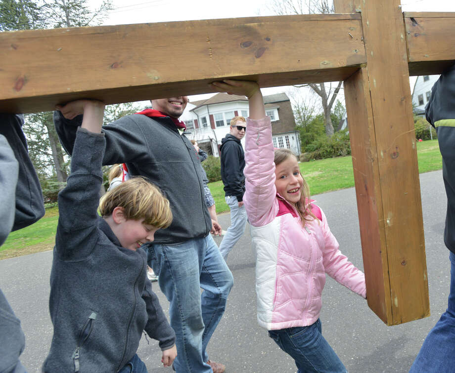 At right, Laura Olmstead, 7, of Riverside, participates in the First Congregational Church of Greenwich Youth Cross Walk in Old Greenwich, Conn., Good Friday afternoon, April 18, 2014. The cross was carried from the church in Old Greenwich to Greenwich Point, where it will be used for the sunrise service on Easter Sunday morning. Photo: Bob Luckey / Greenwich Time