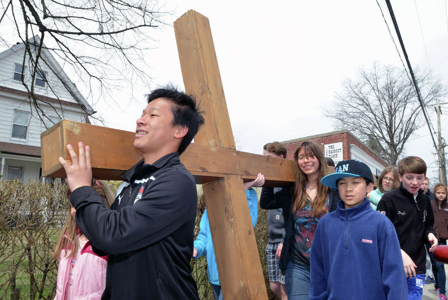 At left, Charlie Teeters, 15, leads the First Congregational Church of Greenwich Youth Cross Walk on Sound Beach Avenue in Old Greenwich, Conn., Good Friday afternoon, April 18, 2014. The cross was carried from the church in Old Greenwich to Greenwich Point, where it will be used for the sunrise service on Easter Sunday morning. Photo: Bob Luckey / Greenwich Time