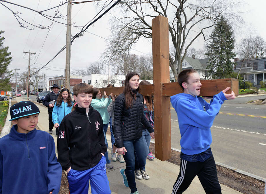 At right, Daniel Lepoutre, 15, leads the First Congregational Church of Greenwich Youth Cross Walk on Sound Beach Avenue in Old Greenwich, Conn., Good Friday afternoon, April 18, 2014. The cross was carried from the church in Old Greenwich to Greenwich Point, where it will be used for the sunrise service on Easter Sunday morning. Photo: Bob Luckey / Greenwich Time