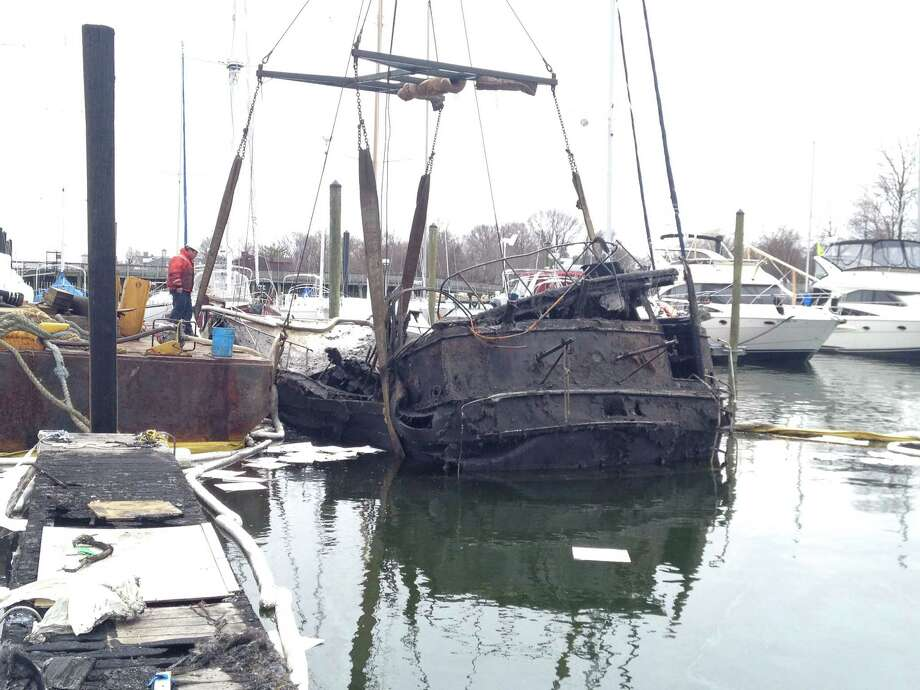 A salvage boat lifts the burnt wreckage of a 46-foot Chris-Craft cabin cruiser from the West Branch of Stamford Harbor Friday morning as part of an ongoing investigation into a fire that destroyed two boats on April 2. Photo: John Nickerson / Stamford Advocate