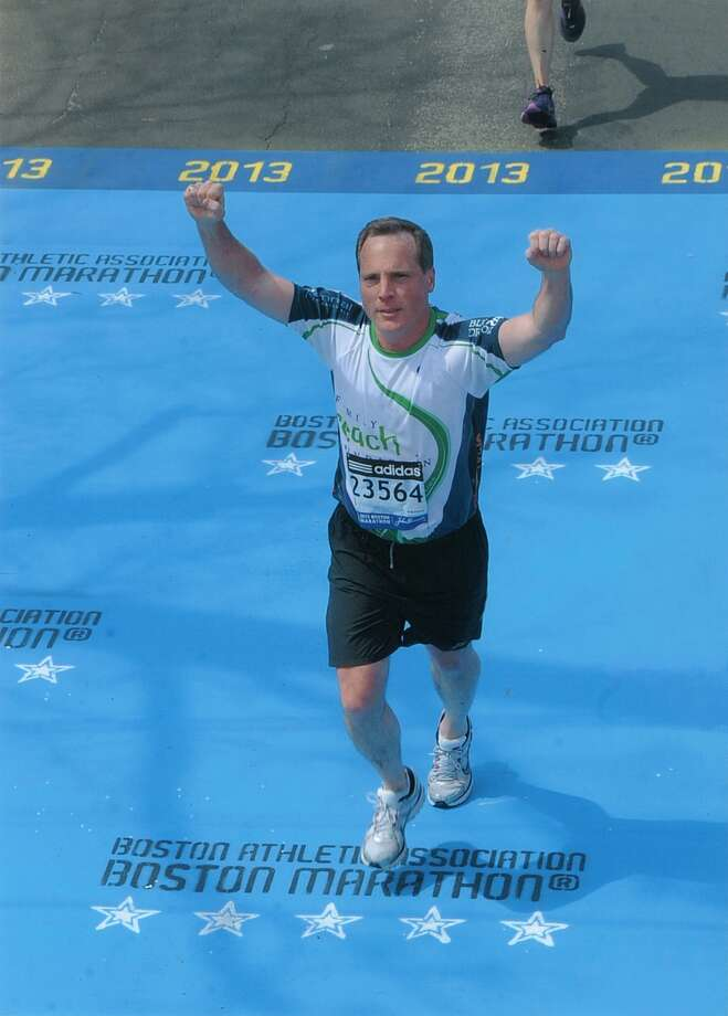 Tom Beusse of Westport crossing the finish line of the 2013 Boston Marathon.