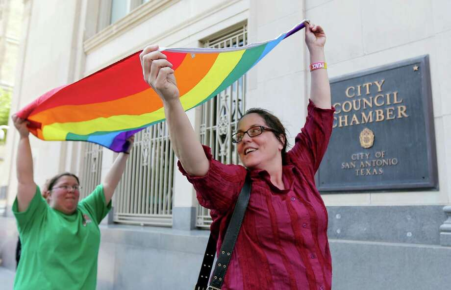Julie Pousson, right, and Jennifer Echeverry, left, celebrate after a non-discrimination ordinance was passed by the San Antonio city council, Thursday, Sept. 5, 2013, in San Antonio. The ordinance in part will prohibit discrimination based on sexual orientation and gender identity. (AP Photo/Eric Gay) Photo: Eric Gay, STF / AP