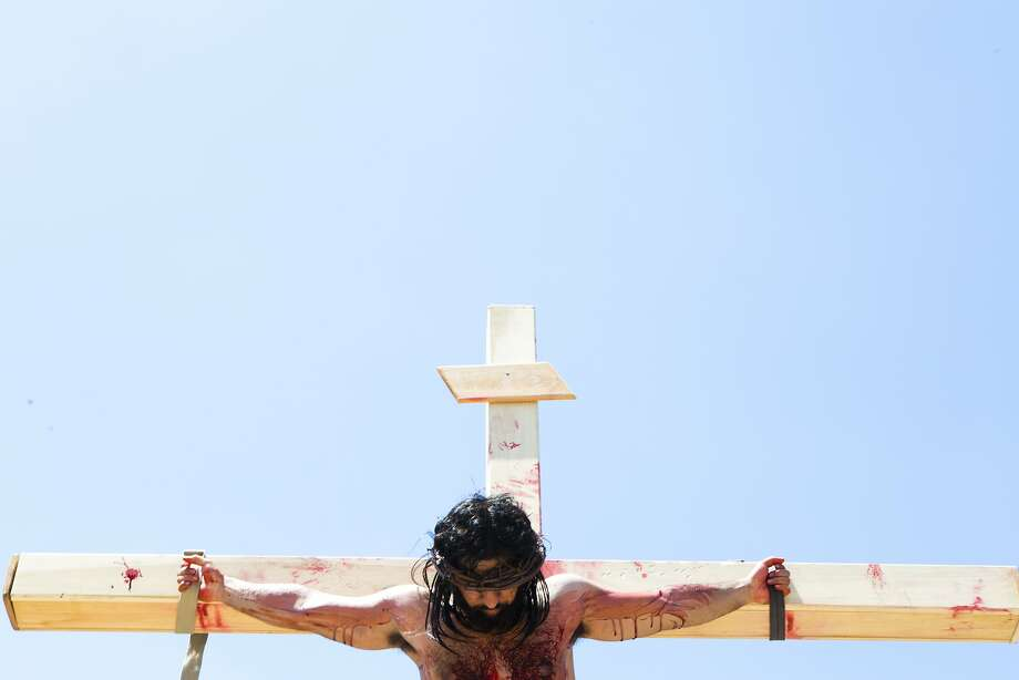 Jesus Estrada, a member of the Queen Of Peace Catholic Church, reenacts the pain Christ went through on the cross on Good Friday, Friday, April 18, 2014, in Houston. Hundreds of followers were present to witness the re-enactment and reaffirm their faith. Photo: Marie D. De Jesus, Houston Chronicle