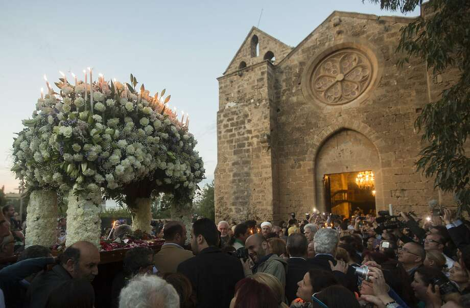 Cypriot Christian Orthodox devotees carry a bier depicting Christ's preparation for burial during a Good Friday procession, at the Ayios Georgios Exorinos Church in the Cypriot Turkish controlled North on April 18, 2014 in Famagusta, Cyprus.  More than 4000 people attended the service, the first since 1957 at the church in the medieval town. Organizers tried to make the Good Friday service an example of how religion can bring both sides together. Photo: Andrew Caballero-Reynolds, Getty Images