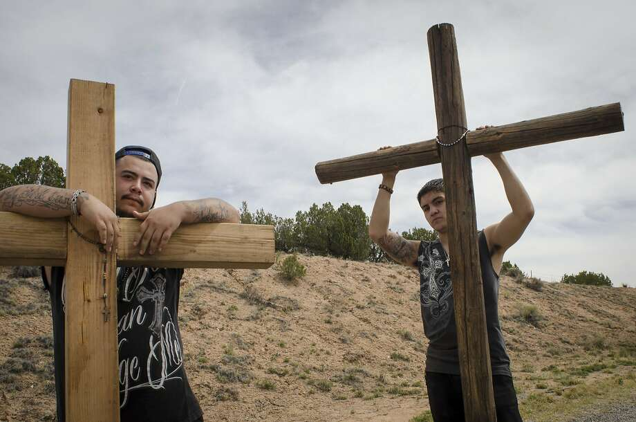 "Bearing the weight of wooden crosses, Troy Martinez, left, and Nick Ortiz travel the ""High Road to Taos"" for the third consecutive year en route to El Santuario de Chimayo, N.M., on Good Friday, April 18, 2014. Many pilgrims carry rosaries and crosses to pray for and honor loved ones. (AP Photo/Jeremy Wade Shockley) Photo: Jeremy Wade Shockley, Associated Press"