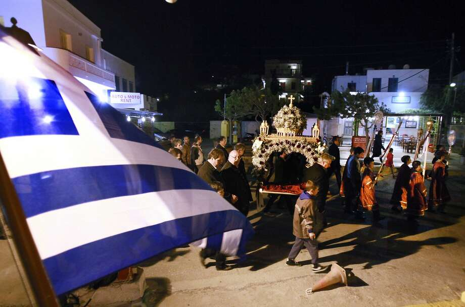 Worshipers walk around the decorated bier during a Good Friday processions, in the port of Katapola, at the Greek island of Amorgos on Friday, April 18, 2014. More than 250 million Orthodox Christians worldwide will celebrate Easter this year on Sunday, April 20. ( Photo: Dimitri Messinis, Associated Press