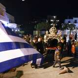 Worshipers walk around the decorated bier during a Good Friday processions, in the port of Katapola, at the Greek island of Amorgos on Friday, April 18, 2014. More than 250 million Orthodox Christians worldwide will celebrate Easter this year on Sunday, April 20. (