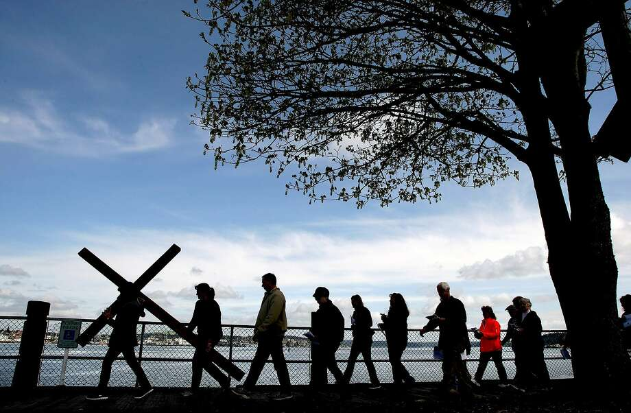 On Good Friday, Monica Beckham carries a cross along the Port Orchard, Wash. waterfront at the 22nd annual Crosswalk followed by other worshippers on Friday, April 18, 2014. The event was held to celebrate the death, and resurrection of Jesus Christ for the upcoming Easter holiday. Photo: Larry Steagall, Associated Press
