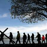 On Good Friday, Monica Beckham carries a cross along the Port Orchard, Wash. waterfront at the 22nd annual Crosswalk followed by other worshippers on Friday, April 18, 2014. The event was held to celebrate the death, and resurrection of Jesus Christ for the upcoming Easter holiday.