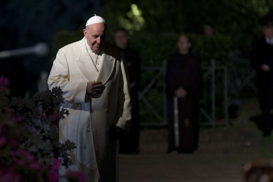 Pope Francis arrives for the Via Crucis (Way of the Cross) torchlight procession to be celebrated in front of the Colosseum in Rome, Friday, April 18, 2014. Pope Francis is presiding over a torch-lit Way of the Cross procession at the Colosseum marking Good Friday in Rome. The pope's resolve to focus the Catholic church's attention on those who suffer was reflected in meditations read aloud to commemorate Jesus' crucifixion. Photo: Alessandra Tarantino, Associated Press