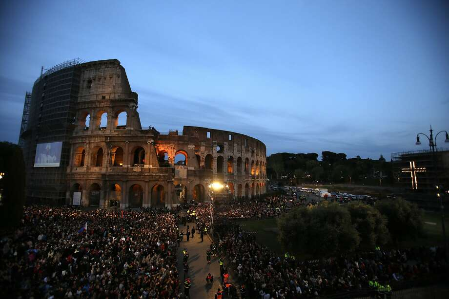 Faithful wait for the start of the Via Crucis (Way of the Cross) torchlight procession to be celebrated by Pope Francis in front of the Colosseum on Good Friday in Rome, Friday, April 18, 2014.  Photo: Alessandra Tarantino, Associated Press