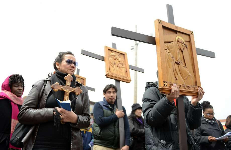 Decey Morales, of Bridgeport, carries a wooden crucifix during the Good Friday Passion of the Lord Multi-lingual Stations of the Cross Procession from St. Augustine Cathedral to St. Patrick Church Friday, April 18, 2014, in Bridgeport, Conn. Photo: Autumn Driscoll