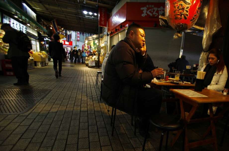 "Japan: People sit at a table outside a restaurant bar at ""Ameyoko"" market place in Tokyo, Friday, April 18, 2014. Ameyoko is a big bazaar in the city selling everything from food, clothing, and jewelry at bargain prices. Photo: Junji Kurokawa, Associated Press"
