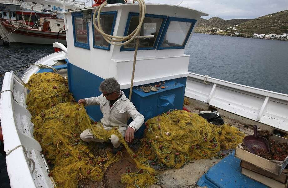 Greece: A fisherman untangles his nets aboard his traditional trehantiri fishing boat at the port of Katapola, in the Greek island of Amorgos. Photo: Dimitri Messinis, Associated Press