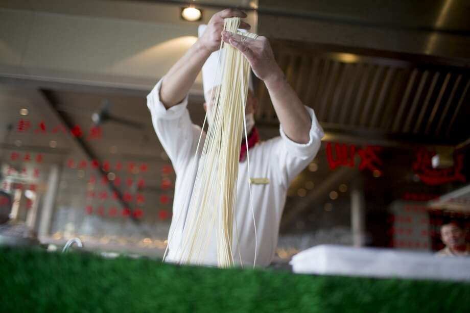 China: A chef makes hand-pulled noodles inside a restaurant at Mission Hills Resort Haikou in Haikou, Hainan Province, China. Photo: Brent Lewin, Bloomberg