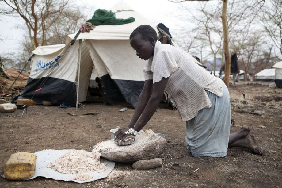 Sudan: A young South Sudanese woman grinding grain donated by the United Nations World Food Programme (WFP) Photo: ZACHARIAS ABUBEKER, AFP/Getty Images